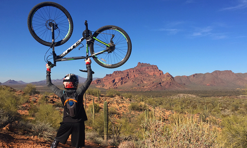 Man holding his bicycle above his head in Sedona, Arizona