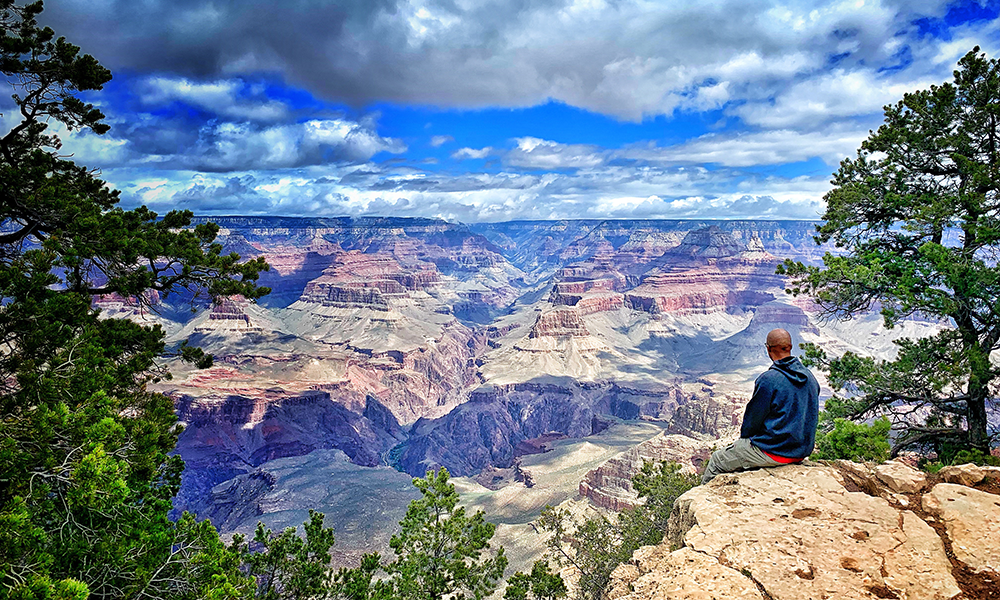 Man sitting at edge of Grand Canyon