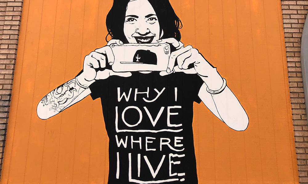 "Danny Martin mural - woman holding smart phone with shirt saying ""Why I love where I live"""