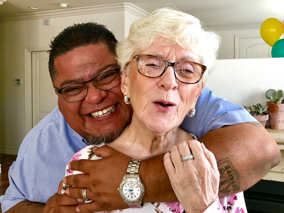 Man smiling and hugging his mother - Adult and eldercare support