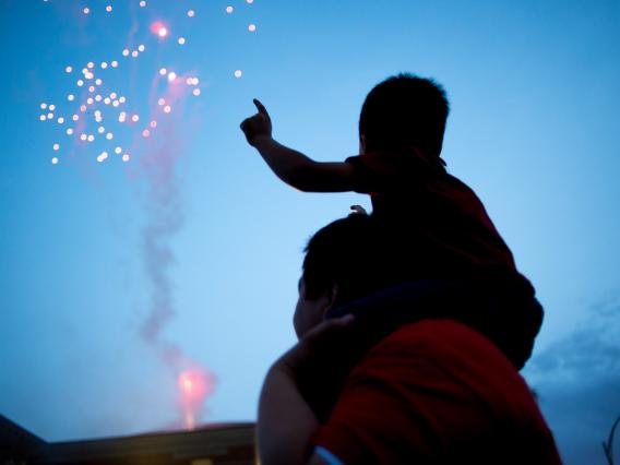 Silhouette of a father with son on shoulders watching fireworks
