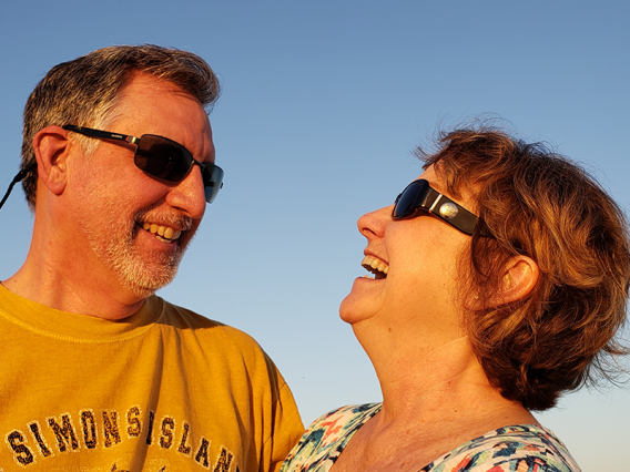 Laughing retired couple outside with sunglasses